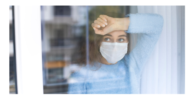 A woman wearing a mask looks out a large window