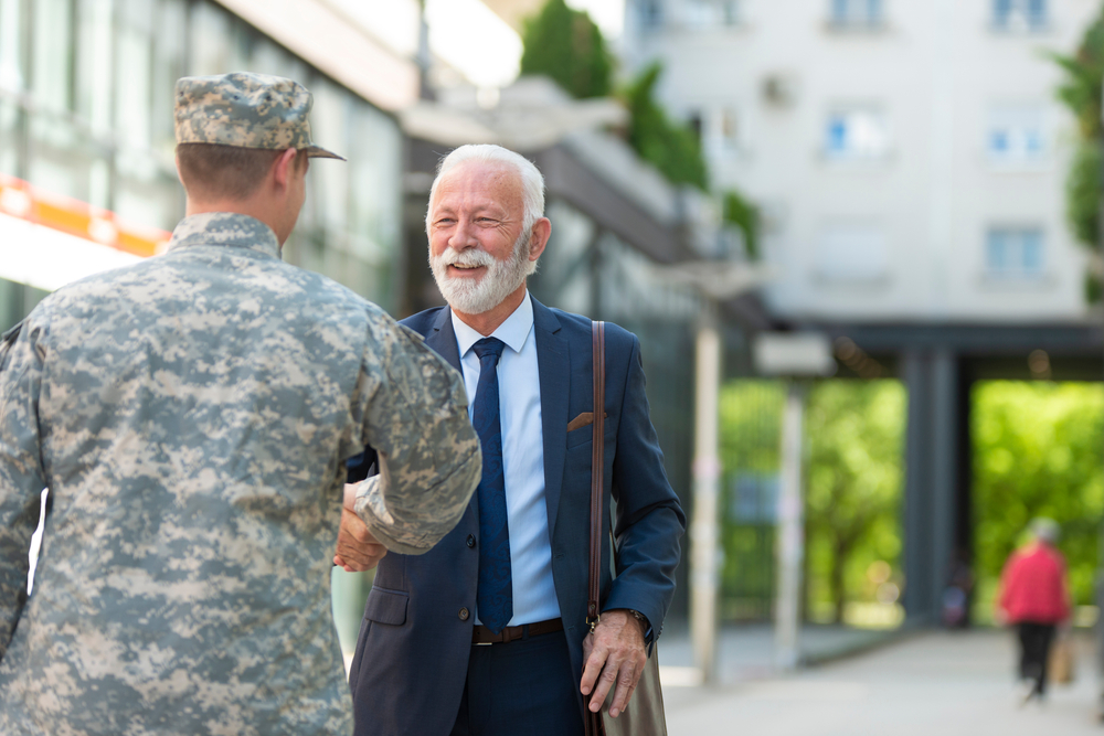 A student veteran and professor shaking hands