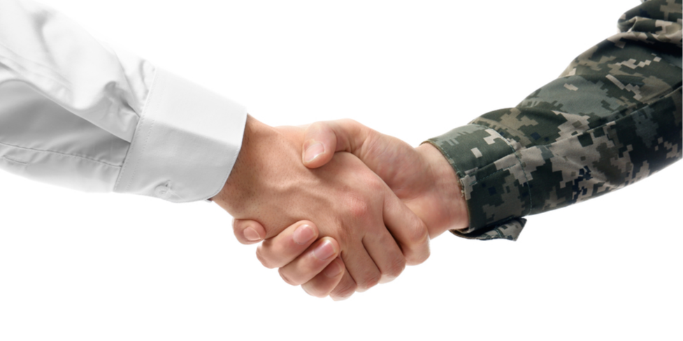 A civilian and service member shaking hands